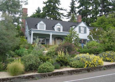 Drought tolerant plants chosen by the owner frame the house in this North Seattle garden