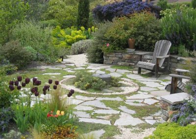 A patio with stone paving gives a focal point to a Mediterranean garden in Seattle