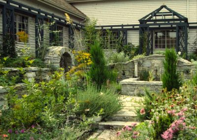 Stonework lends antiquity while the arbors and trellises add interest to the formerly stark walls of the house