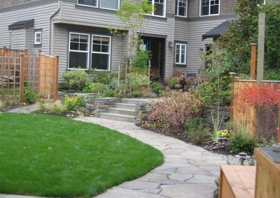 The fence removed, two yards are combnied into one, joined by a curving stone path